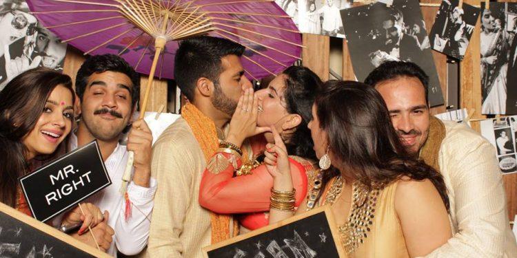 Sheena and Raj Sakaria steal a kiss in this familt portrait.