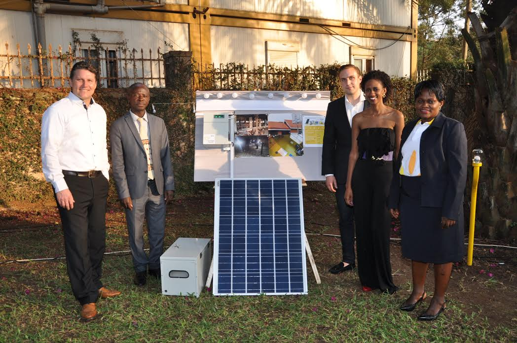 (L-R) Village Power Uganda CEO, Thomas Huth, Commissioner for Renewable Energy John Tumuhimbise, Simon Koch; COO Village Power, Sumaya Kiwanuka; Head of Human Resources and Communication, Village Power and Lilian Babona; Country Manager, Village Power pose besides one of the Company's solar panels and products.