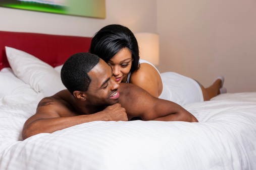 Smiling couple laying on bed