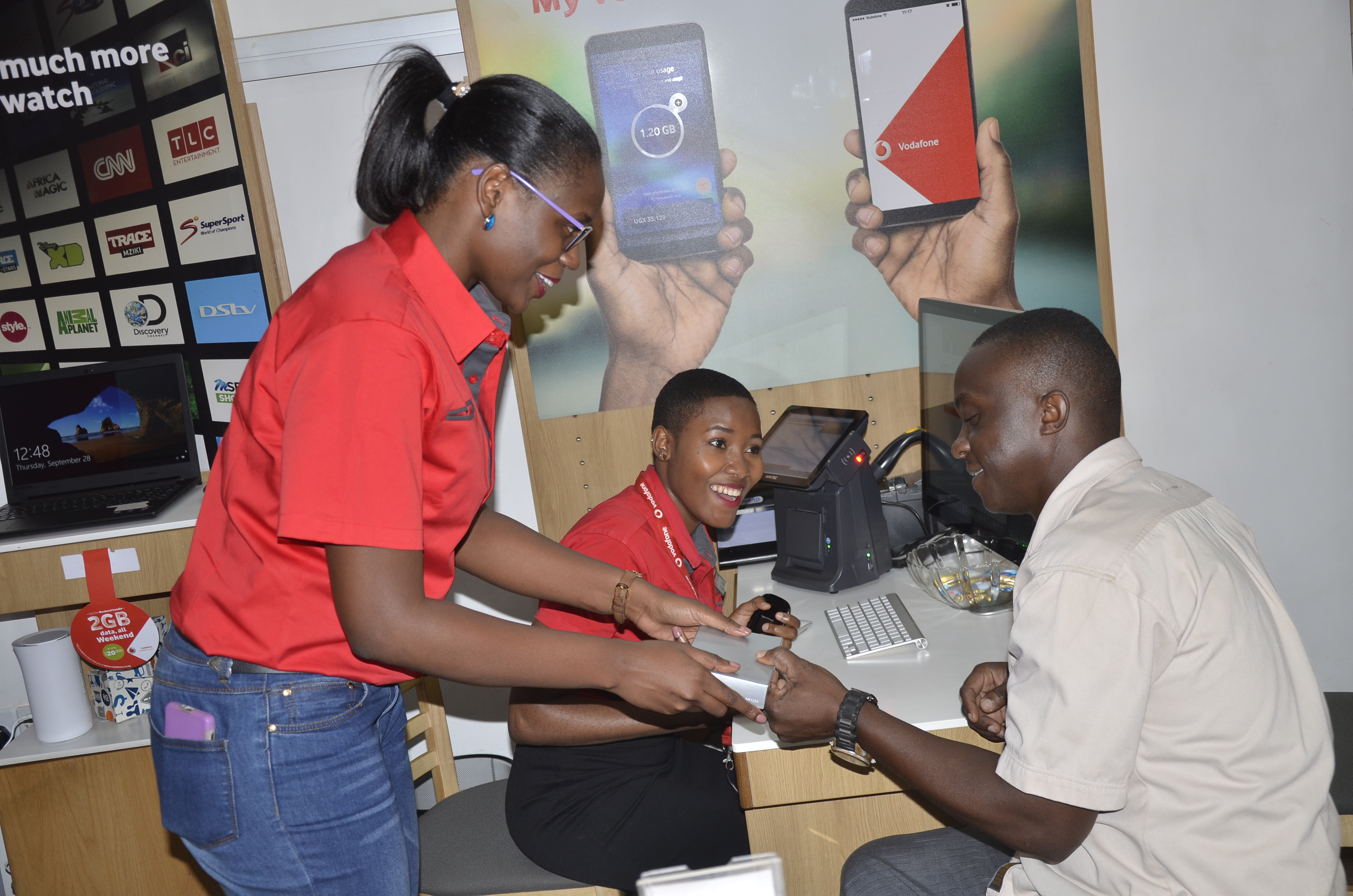 Vodafone customer Kisekka Roddy (right) receives a gift from Vodafone Financial Accountant Lucy Kabugho (left) while Retail Store Agent Stella Namakula (centre) smiles on at the Vodafone Shop on Luwum Street, Kampala  during Vodafone's Customer Service Week today. Vodafone is committed to putting its customers' needs first and adding value to them above everything else.