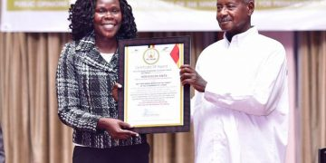 President Yoweri Museveni handing over the best performing minister to Privatisation and Investment Minister Evelyn Anite.