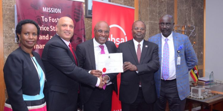 BoU Deputy Governor Dr Louis Kasekende handing over the licence to Absa Managing Director Nazim Mahmood.