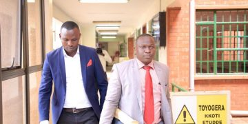 Alex Esagala with his lawyer the day he filed the suit at High Court in Kampala. COURTESY PHOTO.