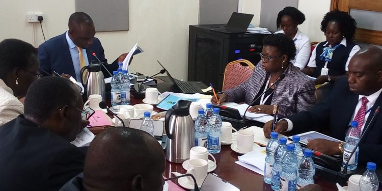 URA Commissioner General Doris Akol with members of the Parliamentary Finance Committee at Parliament today.