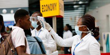 FILE PHOTO: A health worker checks the temperature of a traveller as part of the coronavirus screening procedure at the Kotoka International Airport in Accra, Ghana January 30, 2020. REUTERS/Francis Kokoroko/File Photo - RC2EUE9X5YKK