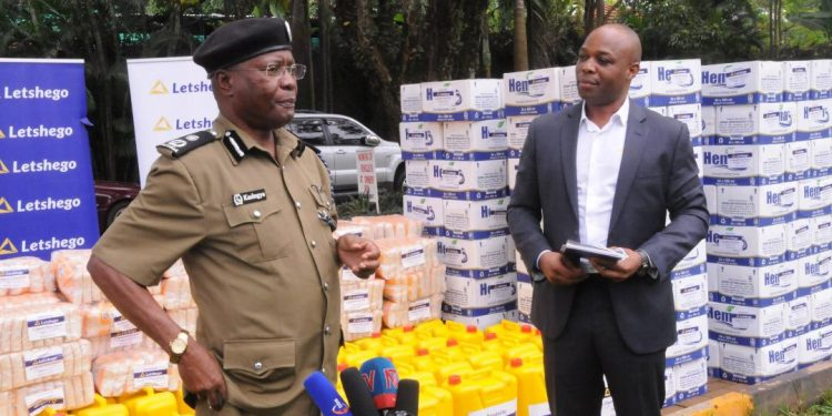 AIGP Asan Kasingye applauds Letshego Uganda for their generous offer to the Uganda Police worth $10000 towards the control of COVID-19. Looking on is Letshego CEO Giles Aijukwe.