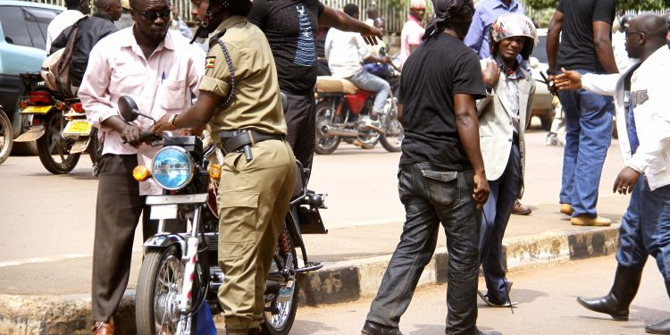The unidentified men in black surrounding a boda boda cyclist after they beat him up and Deputy RPC Kampala south Geoffrey Tayeebwa assisting them to take the boda boda PHOTO BY ABUBAKER LUBOWA