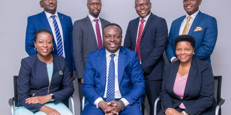 PostBank Uganda's Executive Committee. Sitting, left to right: Judy Namanda Kikonyogo the Chief HR and Administration Officer; Julius Kakeeto, the Managing Director/CEO and Justine Tumuheki Wabwire, the Chief Legal Officer and Company Secretary. Standing, at the back; left-right is: Andrew Agaba, the Chief Business Officer; Andrew Kabeera, Executive Director and Chief Operating Officer; Ssenyange Peter, Chief Finance Officer and Martin Mugisha, the Chief Risk Officer