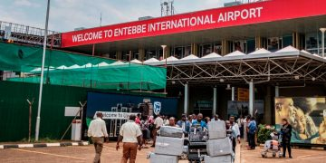 Passengers arriving on international flights leave the international arrivals lobby after they have been screened and cleared for any symptoms of the novel coronavirus at Entebbe Airport on March 3, 2020. - The deadly virus has marched well beyond China's borders, spreading across Asia and Europe and into Latin America, Africa and the United States. More than 90,000 people have been infected and 3,100 killed since the virus first emerged in China's Hubei province late last year. (Photo by SUMY SADURNI / AFP) (Photo by SUMY SADURNI/AFP via Getty Images)